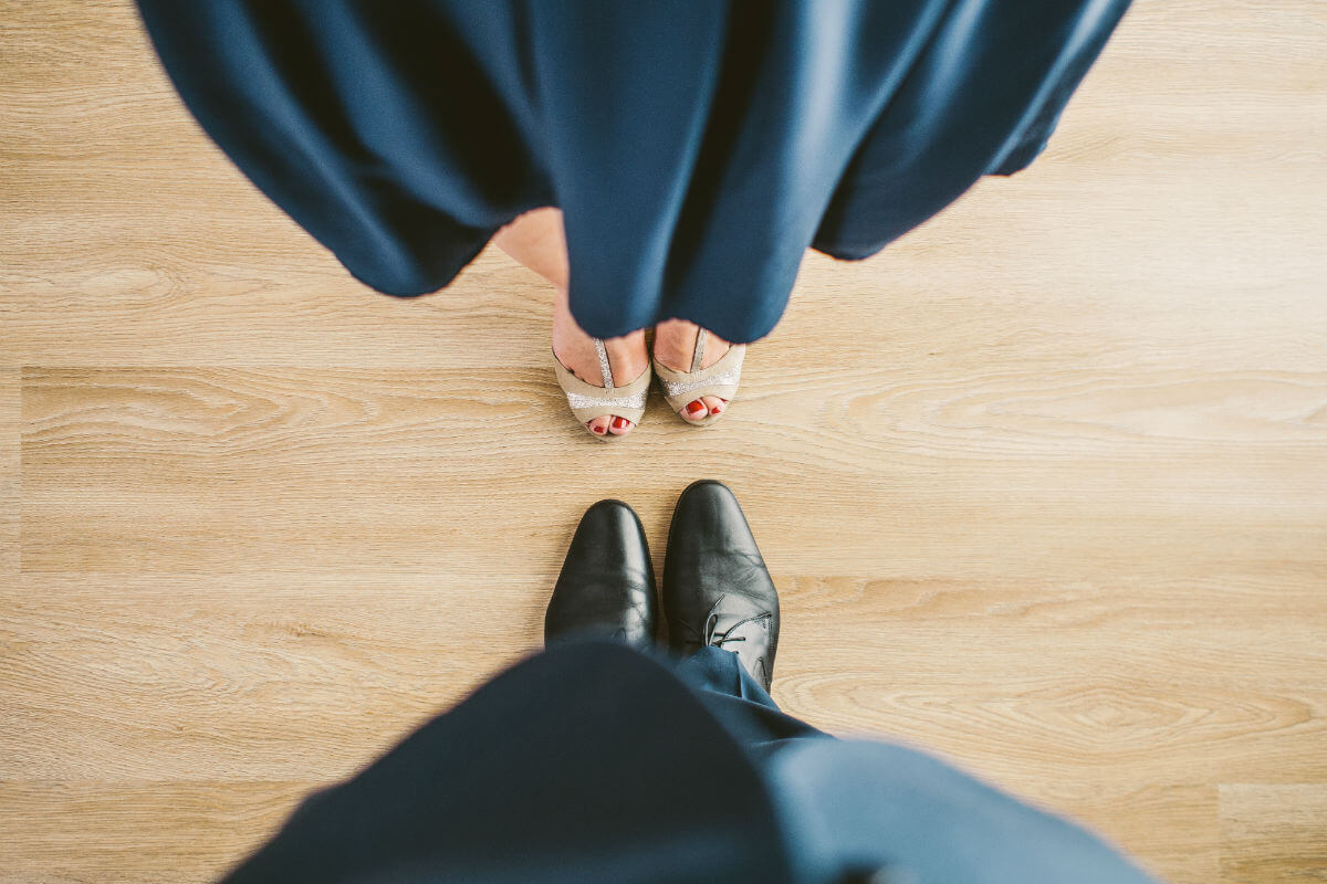 Women in blue dress, man in blue suit toe to toe dancing two-step