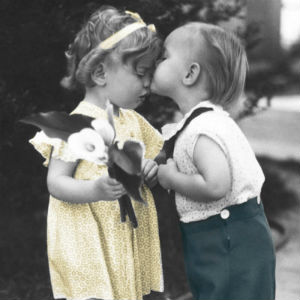 Little girl with flowers being kissed by litle boy