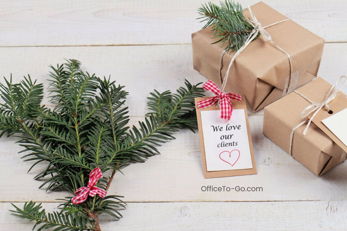 Brown paper wrapped gifts next to pine sprig with red checkered bow