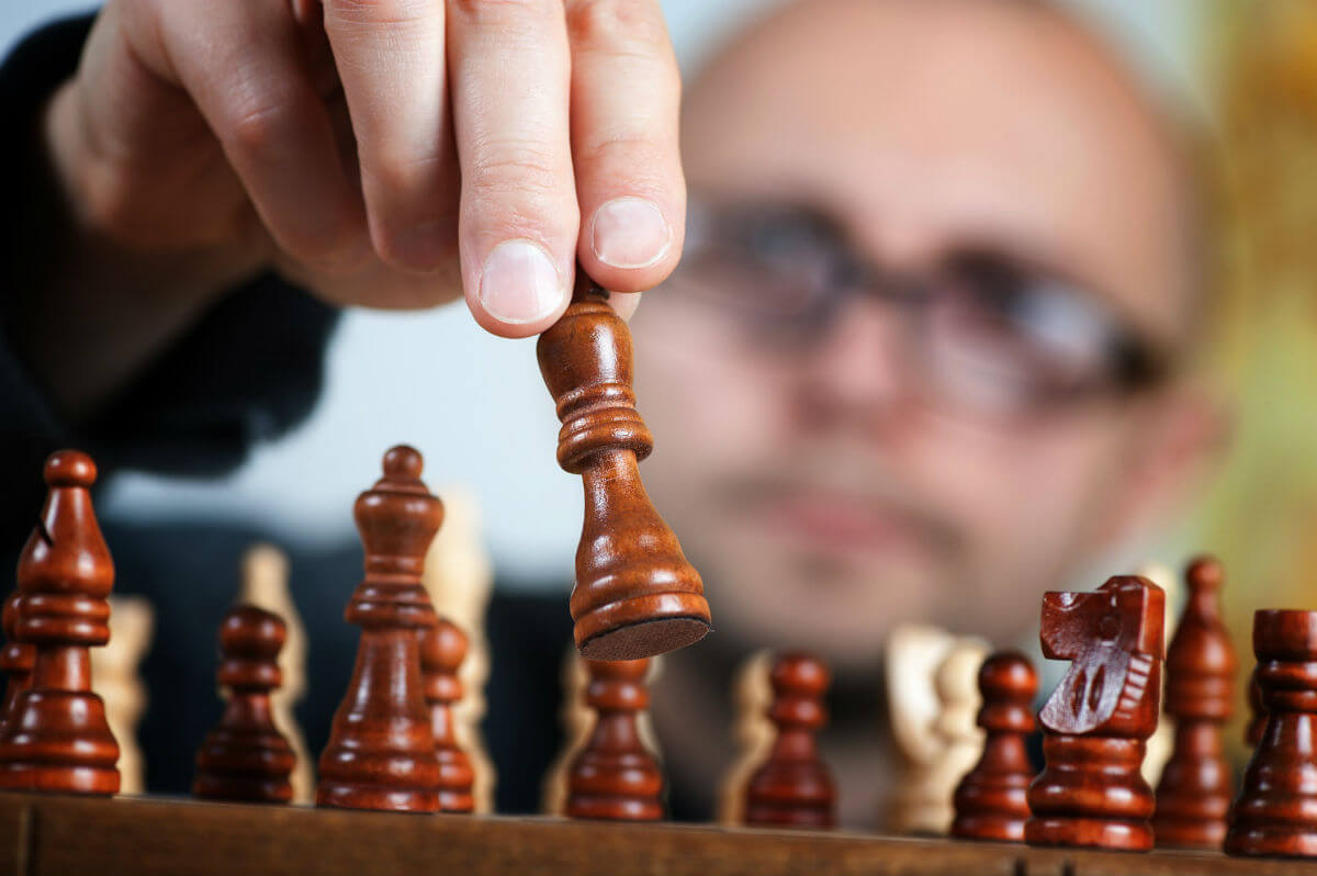 Bald man with glasses thinking about chess goal strategy