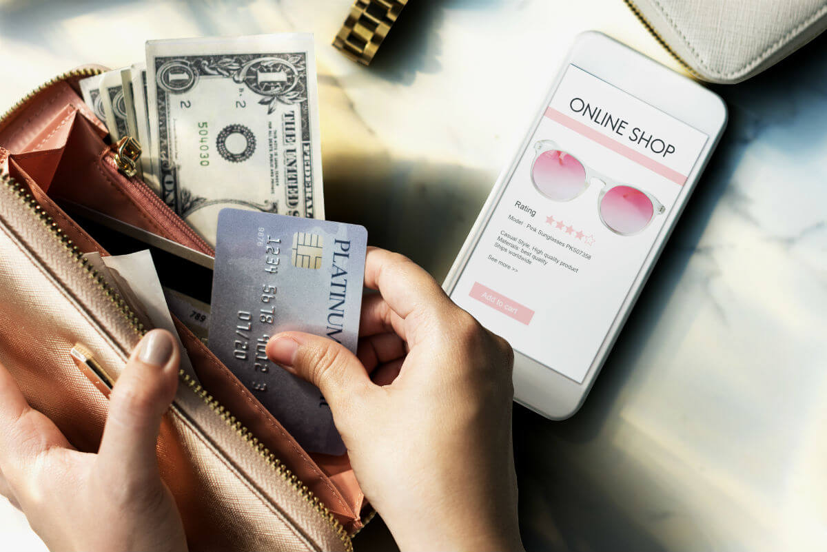 Women taking credict card out of gold wallet with online shop showing on mobile phone