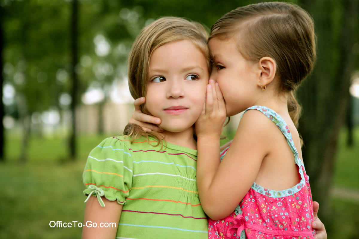 Young girl whispering in the ear of her friend