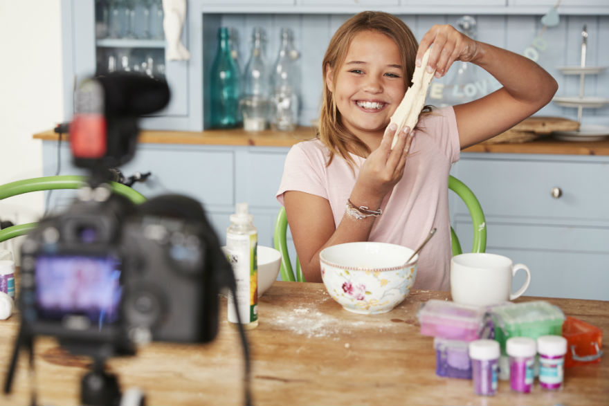 Young girl in kitchen video recording