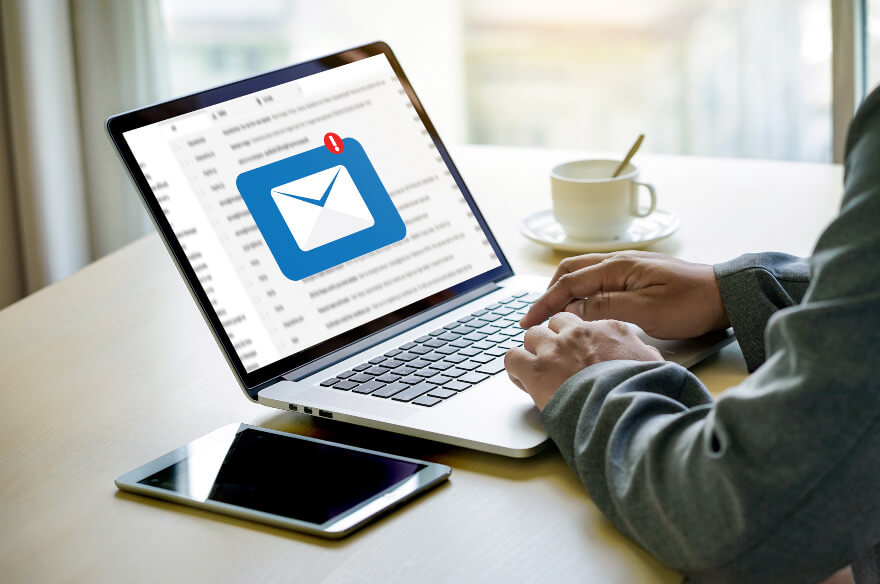Man at laptop with email inbox open